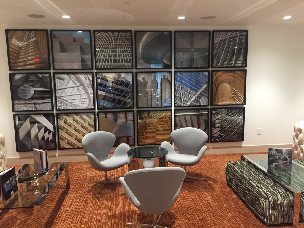 A Hotel Indigo seating area with a wall of photos of Portman signature designs.